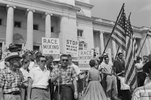 A group of white people with American flags and signs proclaiming