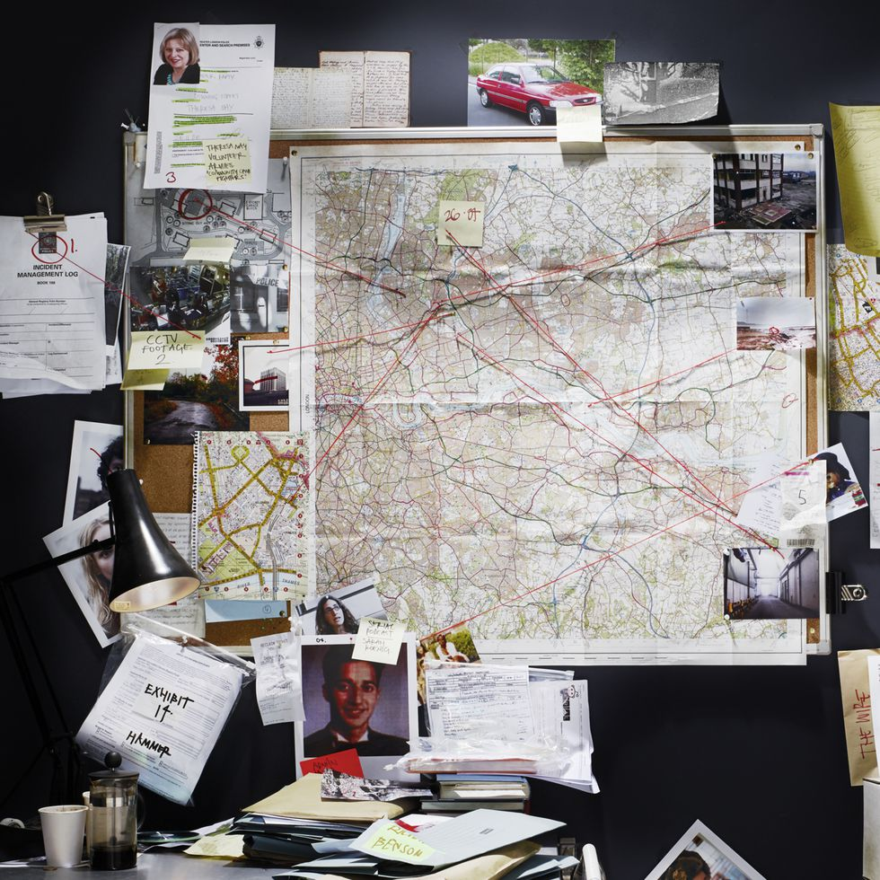 A wall with pictures and maps and documents tacked to it connected by red yarn