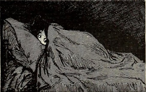 Child huddling under blankets in bed.