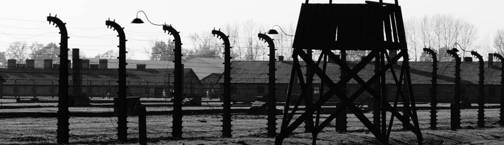 A stark black-and-white photo of a Nazi concentration camp.